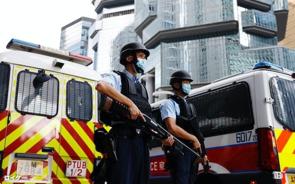 李宇軒被告が乗った車を警備する警察官(19日、香港)=ロイター