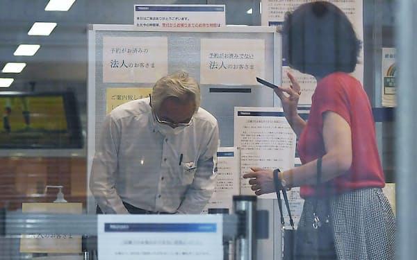 システム障害が発生したみずほ銀行の店舗で利用者に頭を下げる店員(20日午前、東京都中央区)