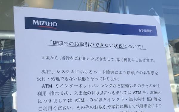 みずほ銀行でシステム障害により店頭取引ができないことを知らせる張り紙(20日午前、東京都港区)