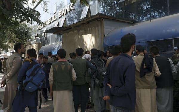 銀行から現金を引き出そうと列をなすアフガン市民ら(15日)=AP