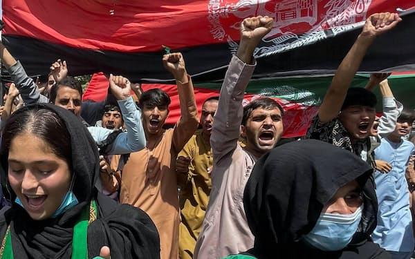 アフガニスタン国旗を掲げ、タリバンの支配に抗議する市民ら(19日、カブール)=ロイター