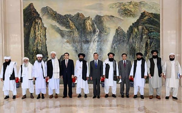 タリバンの代表団と写真に納まる中国の王毅国務委員兼外相(左から7人目)=7月28日、中国天津市(中国外務省のホームページより、共同)