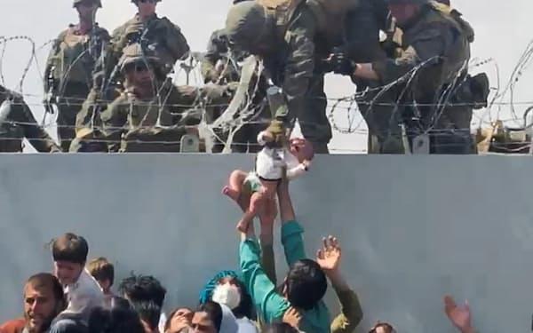 空港で幼児を引き上げようとする米兵(19日、アフガニスタン・カブール)=OMAR HAIDARI・ロイター