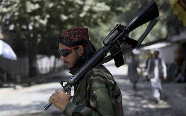 22日、カブール市内に立つタリバン戦闘員=AP