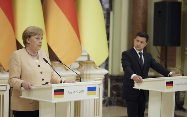 共同会見するドイツのメルケル首相㊧とウクライナのゼレンスキー大統領(22日、キエフ)=AP