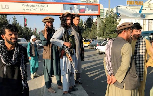 カブール国際空港で銃を持って通りを見張るタリバンのメンバー(中央)=ロイター