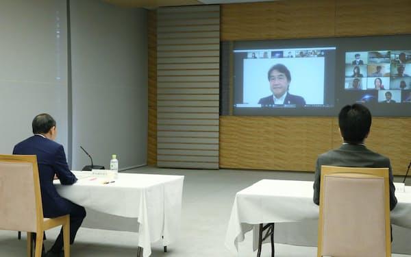 オンラインで開かれた規制改革推進会議で新議長に選出されたKADOKAWAの夏野剛社長(奥の画面内)。左は菅首相(23日、首相官邸)