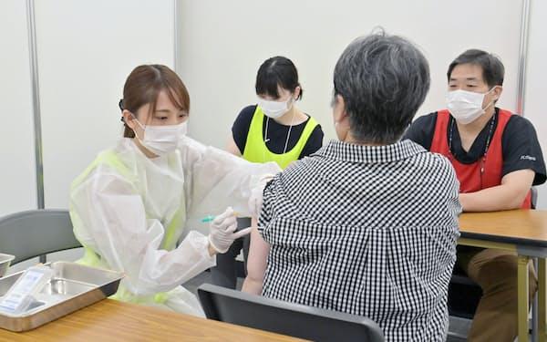 集団接種会場でアストラゼネカ製ワクチンの接種を受ける人(23日午前、大阪市中央区)