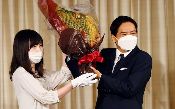 当選を確実にし、花束を受け取る山中竹春氏(右)=22日夜、横浜市
