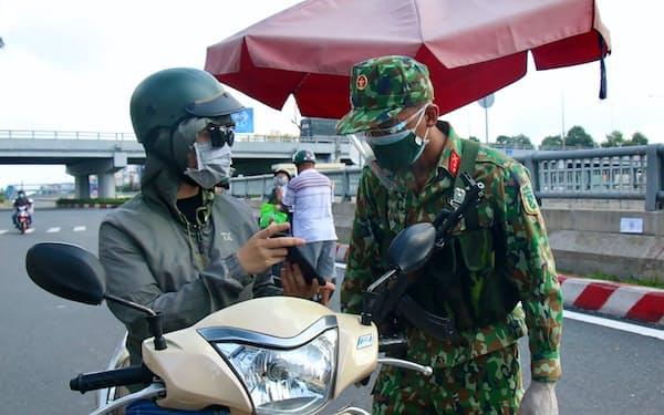 検問では軍の兵士が通行者の身分証明書を確認している(23日、ホーチミン市)=AP