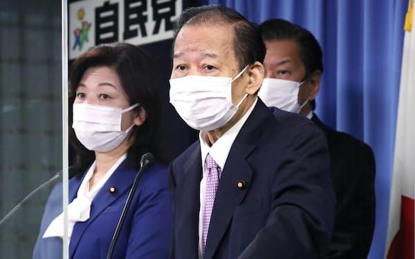 記者会見する自民党の二階幹事長(右、24日午前、党本部)
