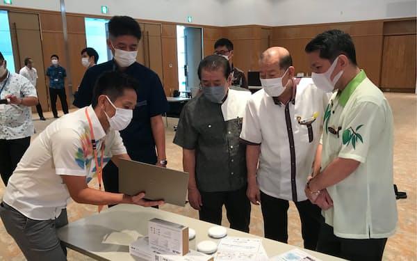 高齢者見守りの実験で使用する機器について説明を受ける沖縄県内3市の市長ら(那覇市)
