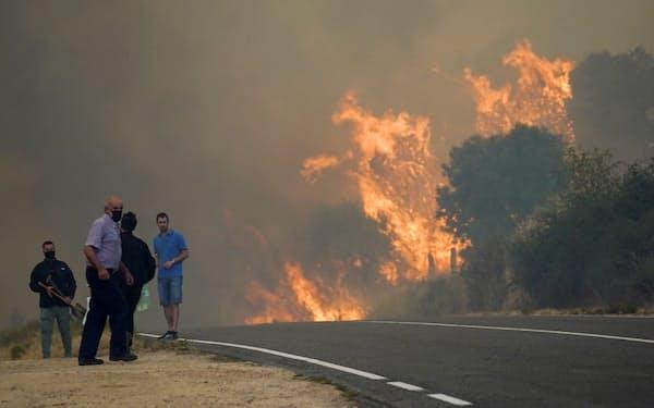 16日、森林火災の状況を見守るスペインの人々=ロイター