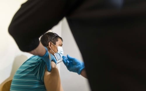 米フロリダ州レイクワースのワクチン接種会場で米ファイザー・独ビオンテック製の新型コロナウイルスワクチンを投与する医療従事者。2021年8月13日金曜日撮影。(PHOTOGRAPH BY SAUL MARTINEZ, BLOOMBERG VIA GETTY)