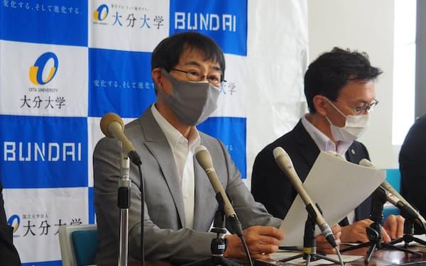 記者会見する大分大学の北野学長㊧(25日、大分市)