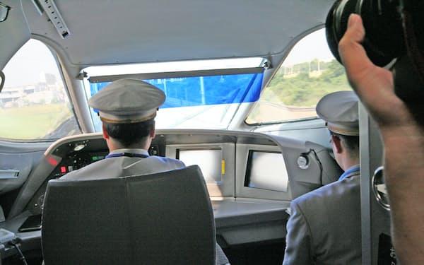 東海道新幹線を走るN700系新幹線電車を運転する運転士。この写真はN700系を用いた試乗列車であるためか、実際の運転操作を担当する運転士のほか、運転部門の管理職も㊨に添乗している。通常の営業運転では運転室には1人の運転士しか乗っていない。(2006年6月7日、筆者が撮影)
