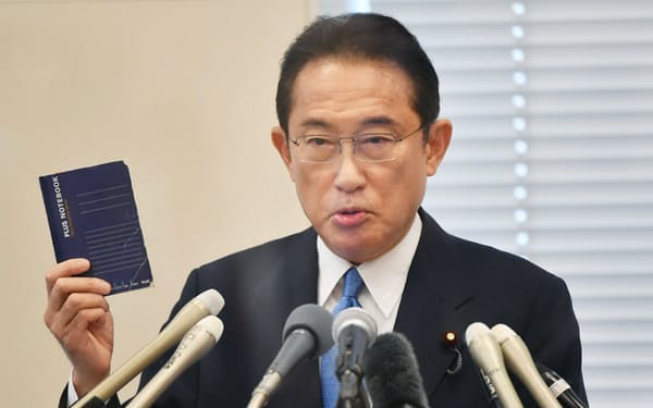 記者会見で総裁選へ出馬を表明し、ノートを掲げた岸田文雄前政調会長(26日、国会内)