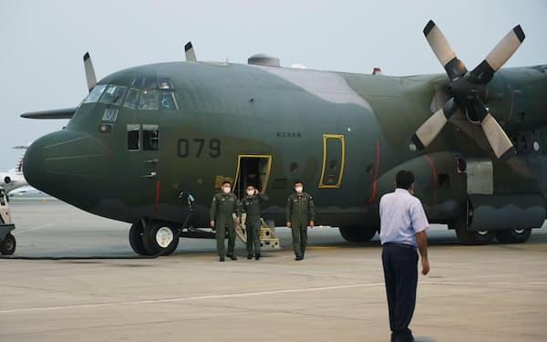 パキスタンのイスラマバード国際空港に到着した航空自衛隊のC130輸送機から降りる自衛隊員ら(25日)=共同