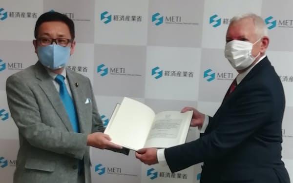 IAEAのグゼリ部長㊨が江島経産副大臣㊧に報告書を手渡した(27日、東京・千代田)