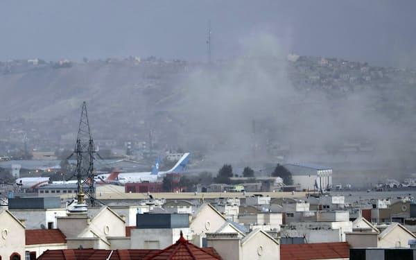 自爆テロ後に煙が上がるカブールの国際空港(8月26日)AP