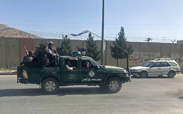 警察車両に乗り首都カブールで移動するタリバン戦闘員=ロイター