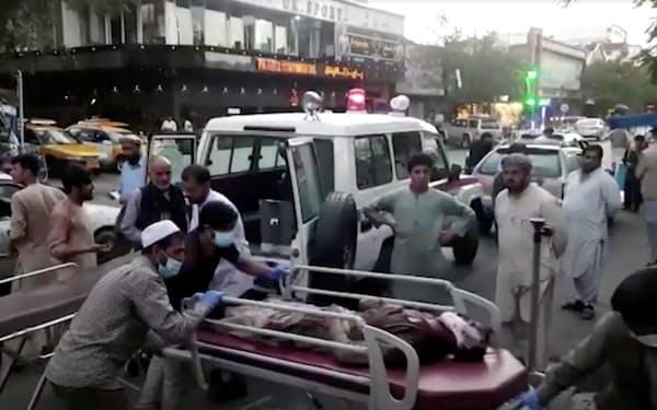 26日、カブールの国際空港付近での爆発後、病院に搬送される負傷者ら(1TV提供)=ロイター