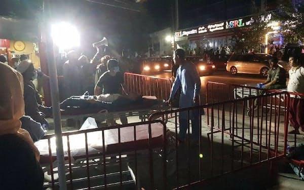 26日、アフガニスタン首都カブールの空港付近での爆発で、負傷者を病院へ運ぶ人たち=ゲッティ共同