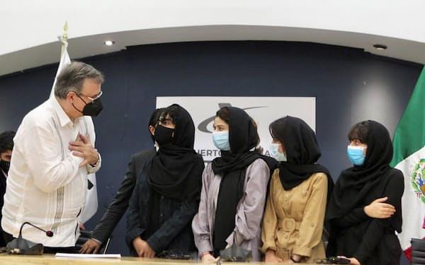 アフガニスタンから逃れた女性を出迎えるメキシコのエブラルド外相㊧(24日、メキシコシティ)=ロイター