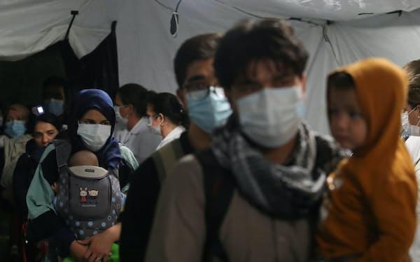 27日、自国を離れ空路で東欧アルバニアに入国したアフガニスタン人=ロイター