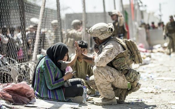 米軍はカブールの国際空港で米国人やアフガン人らの国外退避の支援を続けている(26日)=米海兵隊提供・AP