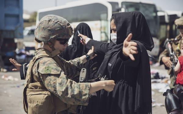 カブールの空港で危険物を所持していないかどうかを確認する米海兵隊員(28日)=米海兵隊提供・ロイター