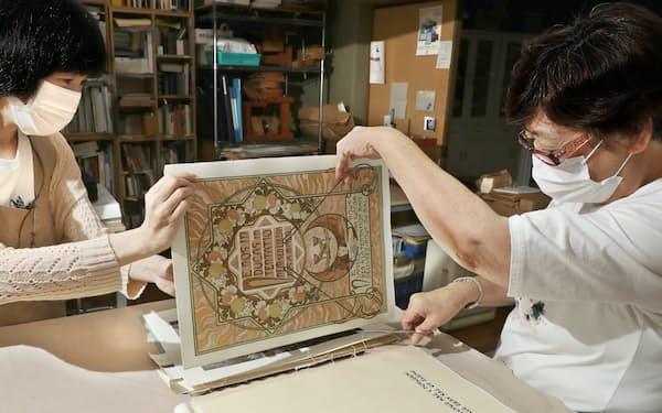 100年以上前にリトグラフで刷られた本。糸でとじられたページを慎重に切り離していく(奈良市)=松浦弘昌撮影