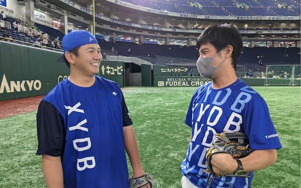 試合前の練習で山崎康晃投手㊧と笑顔で話す三島。選手と近い距離感を心掛けている=球団提供