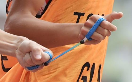 きずなと呼ばれるロープをしっかり握り、伴走者の長谷部匠さん(右)とつながって走る