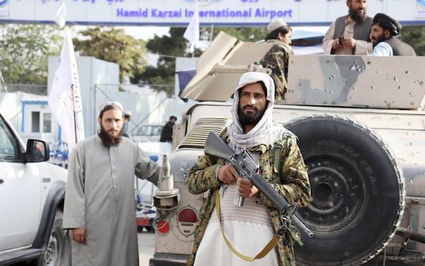 31日、アフガニスタン駐留米軍撤退後、首都カブールの空港前で警備につくタリバンの戦闘員=AP