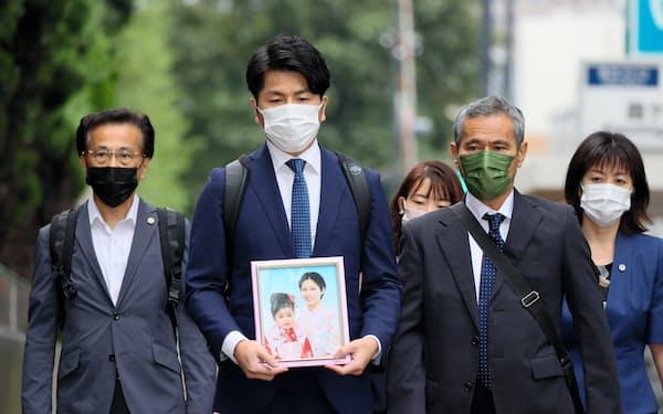 事故で亡くなった妻子の遺影を手に東京地裁に向かう松永拓也さん(左から2人目)