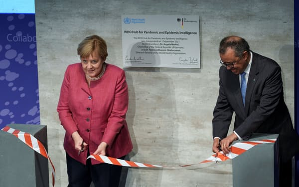 開所式典に参加したWHOのテドロス事務局長㊨とドイツのメルケル首相(1日、ベルリン)=ロイター