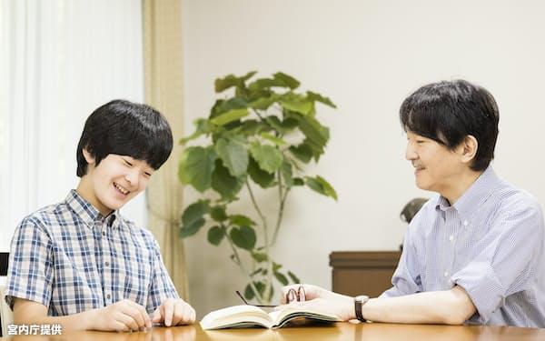 秋篠宮さまと一緒に本を眺める悠仁さま(8月5日、赤坂御用地の御仮寓所)=宮内庁提供