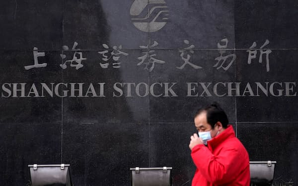 FILE PHOTO: A man wearing a mask walks by the Shanghai Stock Exchange building at the Pudong financial district in Shanghai, China, February 3, 2020. REUTERS/Aly Song/File Photo