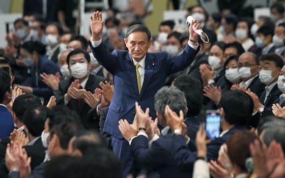 自民党総裁に選出され、両手を広げる菅氏(2020年9月14日、東京都港区)