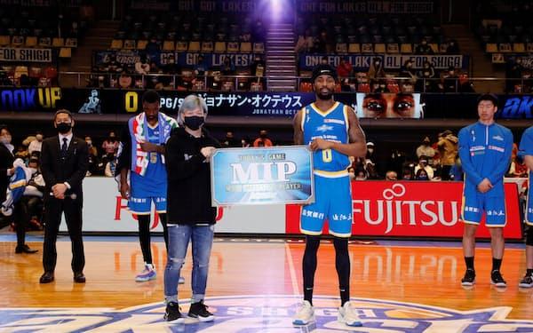 集客を支援する滋賀レイクスターズの選手と記念撮影する宍戸社長(前列左、大津市)