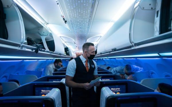 旅客の着席を助ける客室乗務員(米ニューヨーク市)=ロイター