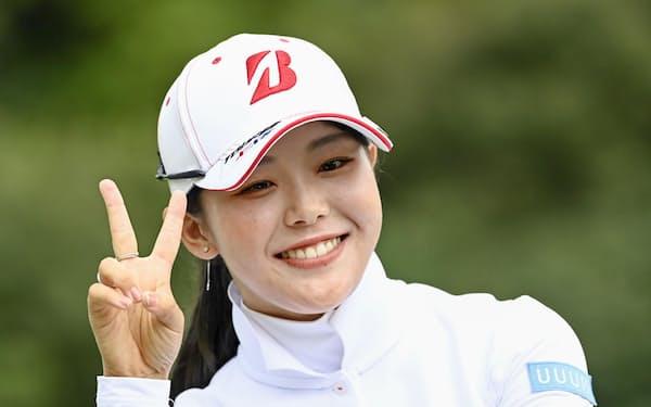 プレーオフを制して優勝し、笑顔で写真に納まる吉田優利(5日、ゴルフ5カントリー四日市)=共同