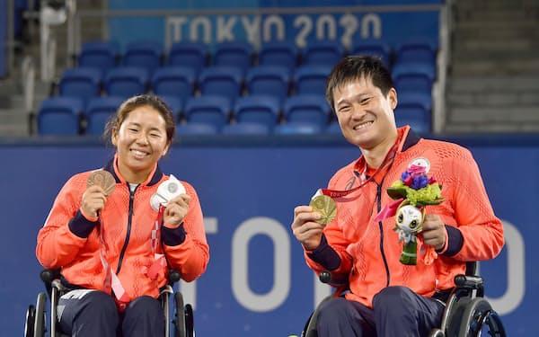 大会で獲得したメダルを手に、笑顔で記念撮影する上地結衣(左)と国枝慎吾=共同