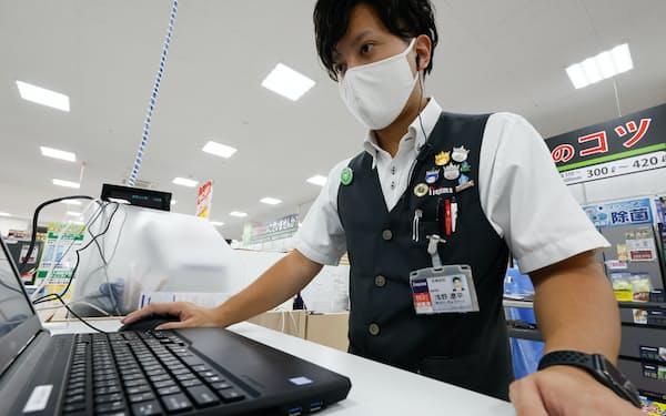 名札にワクチン接種済みのステッカーを貼って店舗に立つノジマの従業員(6日、川崎市宮前区のノジマ川崎水沢店)