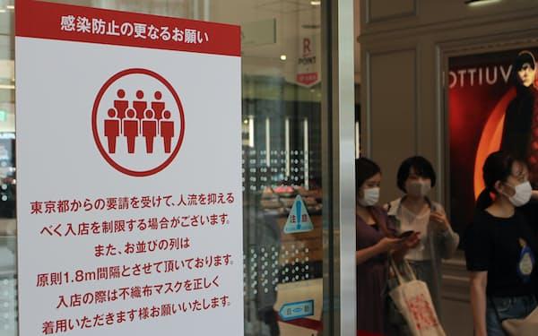 入場制限を示す百貨店入り口の案内(8月)