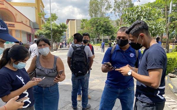 係員の説明を受けてアプリをダウンロードする人々(7日、サンサルバドル)