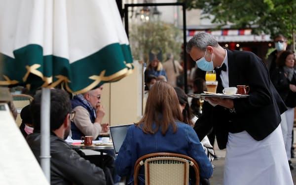 営業を再開した飲食店は人手不足に直面する(パリのカフェ)=ロイター