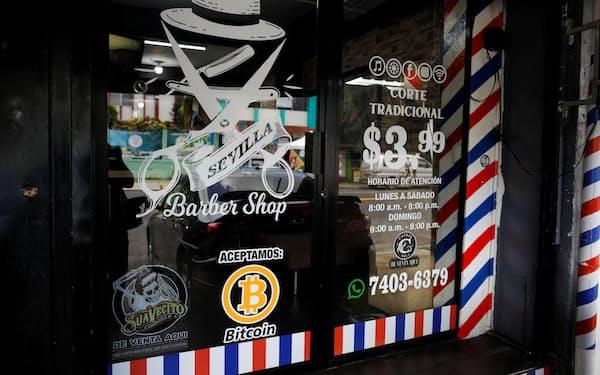 6日、ビットコインを支払いに利用できることを表すロゴを店頭に示すエルサルバドルの理容店(ロイター=共同)