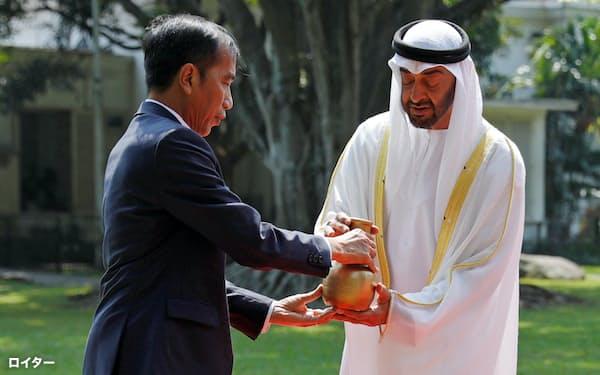 アブダビ首長国のムハンマド皇太子(右)を迎えるインドネシアのジョコ大統領(2019年7月、インドネシア・ボゴール)=ロイター